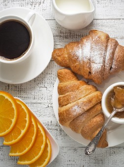 Croissant jam coffee orange jice at white wooden table.